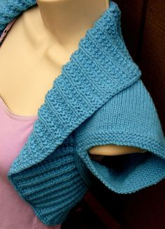 """This lovely Sky Blue Knit Shrug is vibrant and feminine. The arm holes are knitted in a garter stitch, while the body has been knit in a stockinette stitch pattern, with the trim done in a 4"""" moss ribbed stitch, to hug the neck and body. This soft sweater is knit in a light weight yarn, which makes it a year round accessory. This item would be a great gift for someone special or a lovely addition to your own wardrobe. This striking shrug would be a great cover up for bare shoulders, or even…"""