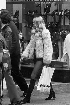 1970s street style. Love black knee high mod boots with a fuzzy jacket and cigarette pants.