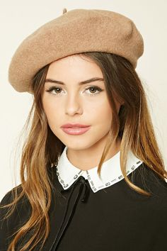A wool beret featuring a pointy accent on top.