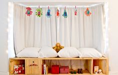 cozy bench with pillows, curtain, banner, and storage, via Pichouline