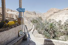 Way between the rocks to the Oasis in Tunisia Africa. Small lake with water and waterfall. Shops and toilletes.