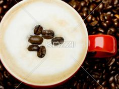 coffee beans in foam - The top of a cappuccino placed in a red mug, decorated and surrounded by coffee Beans