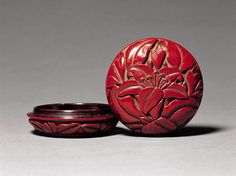 Red Lacquer Perfume Box Carved with Day Lily Design Ming Dynasty Diameter: 6.5cm Height: 3.3cm By the depth of the incisions, this opulently carved lacquer box must have had thirty to forty coatings. The lid and the underside, sumptuously coated with red lacquer, are carved with a spray of day lily against a buff ground. The inside is lacquered in dark brown.