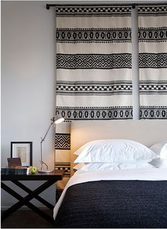 Hang graphic curtains as a headboard focal point in bedroom. Use low profile rods.