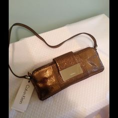 """Calvin Klein Bronze Whipsnake Evening Bag NWT    The most beautiful evening bag! All leather with a modern well organized interior!  9"""" length with shoulder strap drop of 11"""" . Large Gold nameplate with Calvin Klein name plus name stitched into the interior! Soft leather with center zip with room on each side for phone & essentials! Rear outside pocket plus when you open center zip there's another zip for currency, change or ID card! Bronze looks great with everything & this quality Classic…"""