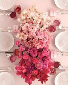 Ombré pink centerpiece of garden roses, phaleonopsis orchids, fringe tulips, and other bulb flowers.