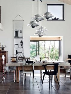 Contemporary dining room with mismatched chairs and industrial chandelier ...