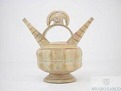 6/ LAMBAYEQUE-SICAN - Botella doble pico asa puente cintada escultórica representando personaje con tocado de media luna, orejeras circulares y pintura facial. Museo Larco