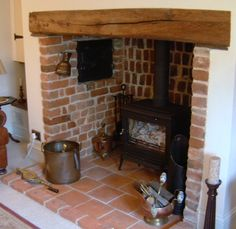 Wood burner placed in existing fire place with wooden lintel and exposed brick interior