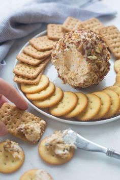 Cheese ball being spread on a cracker with a plate of crackers and the rest of the cheeseball in the background.
