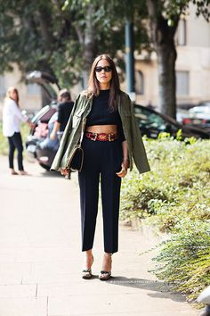 Shop this look on Lookastic: http://lookastic.com/women/looks/cropped-top-and-dress-pants-and-belt-and-sandals-and-crossbody-bag-and-military-jacket/2744 — Black Cropped Top — Black Dress Pants — Red Belt — Dark Green Canvas Heeled Sandals — Black Leather Crossbody Bag — Olive Military Jacket
