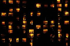 It's a hotel from outside after sunset at Waikiki Beach, Honolulul, Hawaii. I really liked the mosaic pattern of the rooms lit up like little jewelry boxes and people in different poses enjoing the nice evening.