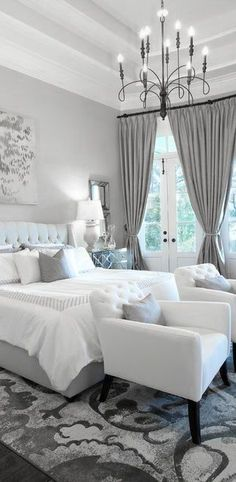 A stunning iron chandelier sets the perfect tone for this gray and white bedroom | Elegant Bedroom | Beautiful Bedrooms | Viyet Style Inspiration