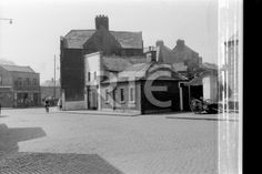 A view of a cobblestoned Thomas Court Bawn near The Coombe, Dublin city, in 1952 or 1953. R Stirling's grocery shop is located at 1a Thomas Court Bawn. The street visible in the left background is Marrowbone Lane; Coombe Dairies is located at number 81. *Note the area of negative damage on the right of frame.* Collection RTÉ Johnson Collection Photographer Johnson, Nevill