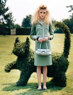 Caroline Trentini stands in front of a cat-shaped topiary. Photographed by Arthur Elgort, Vogue, September 2004.