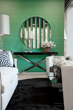 Such a chic room. We love the white couches with the green wall.