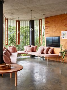 Living room details. The pink curved couch was designed by Anne-Marie, and the coffee table designed and built by Jesse. The plant stands are from Lightly. Photo – Sean Fennessy.