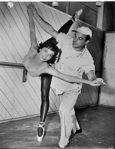 Full BTS shot of Leslie Caron as Lise Bouvier, standing at ballet bar, leg extented, and Gene Kelly as Jerry Mulligan standing behind her. Hollywood Icons, Golden Age Of Hollywood, Hollywood Stars, Hollywood Actresses, Classic Hollywood, Old Hollywood, Gene Kelly, Divas, Fred Astaire