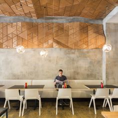 The defunct local brickworks are alluded to in the recycled brick oven surround, ans the owner's metalwork business is represented, too. A timber cladding on the wall and ceiling references the angular intersections outside, and they are echoed in the pendant lights that are suspended beneath...