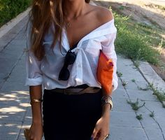 White collared button up shirt tucked in a high waisted black skirt with a brown leather belt and an orange clutch