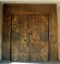 A door carved with pomegranates, grapes, vines, birds, oud player, traditional Armenian symbols. In Yerevan , Armenia.