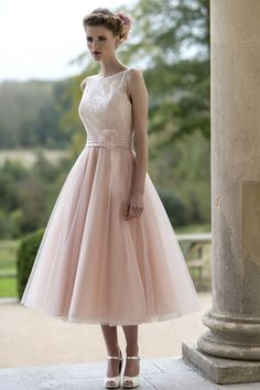 M625 - NEW COLLECTION. T-length bridesmaid dress with delicate lace bodice and sheer neckline and full Tulle Fifties style skirt. Satin waistband with pretty organza flower detail. Zip up back with button trim. #bridesmaids
