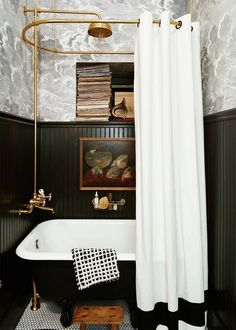 Fornasetti Nuvolette clouds wallpaper in a bathroom, above a clawfoot tub