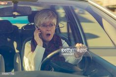 Stock Photo : Frightened senior woman in car on cell phone