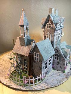 """Denne gang har jeg lavet en lille landsby med Dies fra Tim Holtz, """"Village Manor"""". Til byen har jeg brugt de to grundhuse: """"kirketårnet"""" og """"halloween"""" huset. Jeg har også brugt lidt fra """"slik"""" huset og noget fra """"have"""" sættet. Der ud over har jeg brugt hvid karton og Prima papir. På tagene og skorstene ... Læs mere"""