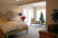 A red poinsettia plant on the nightstand and Christmas tree in the window of the sitting area in this master bedroom in one of our model homes. The drum-shaped table adds a dose of whimsy.