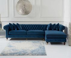 The Fiona Blue Velvet Right Facing Chesterfield Chaise Sofa brings elegance and eye-catching design to every living room setting. Beautifully crafted, the chaise sofa is upholstered in smooth rich blue velvet and boasts a stunning deep-buttoned design and chic scrolled armrests. Completing the look, the Fiona Chaise Sofa features stylish metal stud detailing. Comfort is ensured thanks to foam-filled seat cushions and 6 complimentary throw cushions. This sofa also comes in green or grey. Delivery Blue Velvet Sofa Living Room, Blue Living Room Sets, Velvet Corner Sofa, Blue Couches, Living Room Sofa, Velvet Couch, Living Rooms, Chaise Cushions, Chaise Sofa