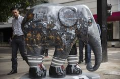 A passer-by looks on an elephant sculpture as part of the 'Elephant Parade' at the Paulista Avenue in Sao Paulo, Brazil, 01 August 2017. Aug. 1, 2017. (Photo: Sebastiao Moreira/EPA/REX/Shutterstock)