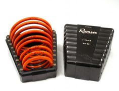 """Diaphragm fitting rings which were used as trial sizes to check for comfort and fit before a CAP was prescribed.    Each of the orange rubber rings is marked Ramses with a trademark encircled """"R"""" and with the size of the ring in mm. The box is marked """"Ramses TM. Reg. US & Can Pat. Off. Fitting Rings"""". 1940-1950."""