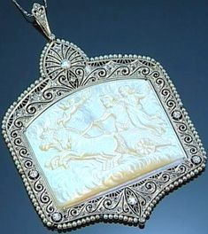 MOTHER-OF-PEARL CAMEO SEED PEARL AND DIAMOND PENDANT CIRCA 1905. The mother-of-pearl cameo depicting a mythological scene within a pierced frame of circular- and rose-cut diamonds and seed pearls on a fine chain necklet cameo signed G. Costa.