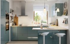 Smart kitchen with KALLARP doors in high-gloss grey-turquoise and upcycled ÖSTERNÄS leather handles and a kitchen island with two stools.