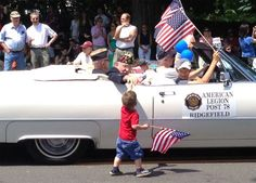 A young boy handed a flag to one of the veterans from the American Legion during this morning's parade. Under a sunny sky, Main Street was packed for the annual Memorial Day celebration that lasted an hour and included thousands of marchers. —Bill Garland photo