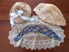 Antique estate lot consisting of 2 ladies Victorian Edwardian hats or caps. The cloche hat is ivoried with age. Hand crocheted with delicate lace net lining. The lace topper cap is light ivoried delicate lace with blue faded ribbon across top and strap on underside covered in lace netting...a perfect re-enactment costume hat. The ecru colored all cotton drawstring purse appears is hand crocheted. The blue satin ribbon is a replacement. Cardboard on interior base is marked with advertisement…