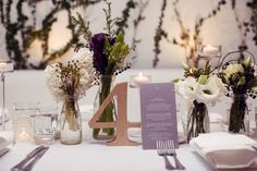 milk bottles with white, green, and purple flowers. Pretty elegant/rustic wedding decor.