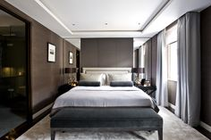In another guest bedroom, Sims Hilditch used darker shades of warm brown and warm gray and mirrored surfaces to create the illusion of space.