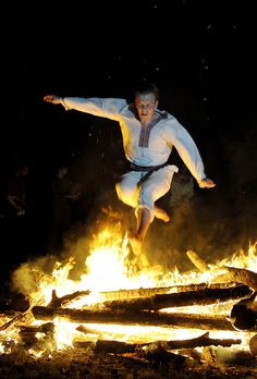 A Belarussian in traditional clothing jumps over a fire while celebrating Ivan Kupala Night, a traditional Slavic holiday, marking midsummer, outside the town of Dobrush on June 24, 2010. During the celebration, originating in pagan times, people plait wreaths, jump over fires, and swim.