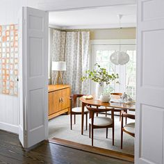 Bifold Dining Room Doors White bifold doors, once leading to an enclosed porch, now create a welcoming entrance into a traditional-meets-modern dining room. The doors help retain the Cape-cod influenced home's original charm. Room Doors, Interior, Wood Doors Interior, Mid Century Modern Dining Room, Door Design Interior, Room Divider Doors, Home Decor, Modern Dining Room, Doors Interior