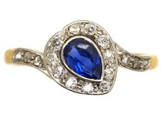 A really pretty and romantic heart shaped ring set with a pear shaped sapphire surrounded by small diamonds. The shoulders are set with rose diamonds. The shank is 18ct gold and the top is platinum. It was made circa 1900-1910.