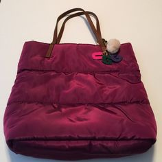 UGG Nylon Handbag. Rare. Purchased in Australia  Wine colored nylon handbag with brown leather straps. Never used. Snap closure with cell phone pockets and zippered pouch. Also has a cute key fob attached with a pom-pom. This is A rare find! Was $149 new. Get a deal here. UGG Bags Shoulder Bags