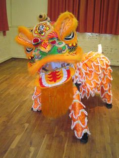 The Southern style costumes feature a lion that more closely resembles Nian, the fierce horned monster that inspired many Chinese New Year traditions  The Southern Lion's head is shaped more like a dragon and has a drape.  It can have two or four legs.  When performing, the Southern Lion thrusts its head to the sound of drums, gongs and cymbals.  The Lion Chinese Lion Dance Southern Style - Dancers must precisely coordinate their movements with those of the instruments