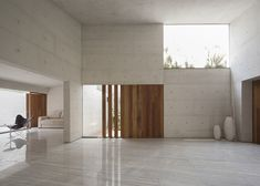 Cap House by MMX Studio - white tiles with white concrete walls and timber highlights