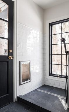 Black and white dog shower in a contemporary mudroom with black slate floor tiles contrasted with white subway wall tiles. A tall black framed window compliments the door making this shower unique and inviting. via - Alec Williams Construction