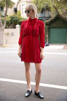 Brooke Testoni wears a red lace mini dress with black loafers, a chain strap cross body bag and Ray Bans
