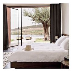 Simple bedroom with a view, white linen bedding, Moroccan rug