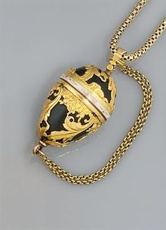 A late 18th century gold, bloodstone and enamel vinaigrette. The egg-shaped bloodstone with applied engraved scroll cagework decoration with white enamel engraved with the legend Gage de Mon Amette, the screw fitting top opening to reveal an interior pierced grill, to loop suspension and later fancy-link neckchain, circa 1790