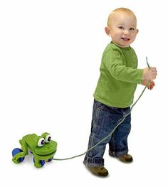 "Frolicking Frog Pull Toy: When pulled by its string, it playfully ""hops"" up and down with wiggling eyes, which adds to the excitement of those early steps."